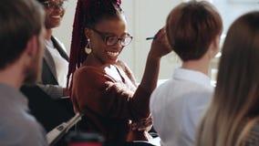 Glückliche lächelnde afrikanische Geschäftsfrau, die auf Seminar im modernen Büro zusammen mit multiethnischem Unternehmensteam h stock footage
