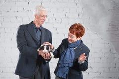 Glückliche lächelnde alte Paare, die zusammen mit Haustierkaninchen auf weißem Ziegelsteinhintergrund stehen Lizenzfreie Stockfotos