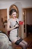 Glückliche lächelnde attraktive Frau, die ein elegantes Kleid und schwarzen Strümpfe sitzen auf der Sofaarmholding einen kleinen  lizenzfreie stockfotos