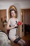 Glückliche lächelnde attraktive Frau, die ein elegantes Kleid und schwarzen Strümpfe sitzen auf der Sofaarmholding einen kleinen  lizenzfreie stockbilder