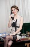 Glückliche lächelnde attraktive Frau, die ein elegantes Kleid und schwarzen Strümpfe telefonisch sprechen in einer Bürolandschaft  lizenzfreie stockfotografie