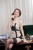 Glückliche lächelnde attraktive Frau, die ein elegantes Kleid und schwarzen Strümpfe telefonisch sprechen in einer Bürolandschaft lizenzfreies stockbild