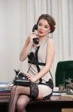 Glückliche lächelnde attraktive Frau, die ein elegantes Kleid und schwarzen Strümpfe telefonisch sprechen in einer Bürolandschaft stockbild