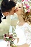 Glückliche lächelnde blonde Braut im weißen Kleid und im Kranz Han küssend Stockfotografie