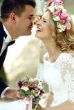 Glückliche lächelnde blonde Braut im weißen Kleid und im Kranz Han küssend Stockfoto