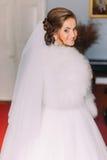 Glückliche lächelnde blonde Braut von der Rückseite in der weißen Kleider-, Schleier- und Pelzboa zuhause Lizenzfreie Stockfotografie
