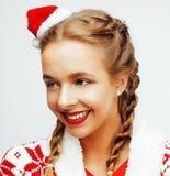 Glückliche lächelnde blonde Frau der Junge recht auf Weihnachten in rotem Hut und in Feiertag Sankt verzierte Plaid, Lebensstille Stockbilder