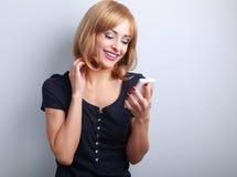 Glückliche lächelnde blonde Frau, die im beweglichen phote auf blauem backgr chating ist Stockfotografie