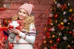 Glückliche lächelnde blonde Frau mit Geschenk auf Heiliger Nacht Stockbild