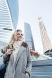 Glückliche lächelnde Blondine im Geschäftszentrum auf Wolkenkratzerhintergrund Lizenzfreies Stockfoto