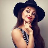 Glückliche lächelnde denkende Make-upfrau in schwarzem elegantem Hut lookin Lizenzfreies Stockfoto