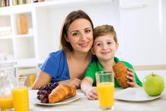 Glückliche lächelnde Familie, die gesundes frisches Frühstück isst Stockfoto