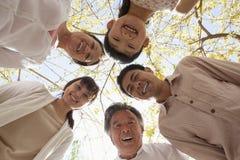 Glückliche lächelnde Familie in einem Kreis, der unten in einem Park im Frühjahr schaut Lizenzfreies Stockbild