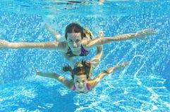 Glückliche lächelnde Familie underwater im Swimmingpool lizenzfreie stockbilder