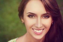 Glückliche lächelnde Frau auf grünem Hintergrund Stockfoto