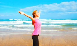 Glückliche lächelnde Frau der Eignung auf dem Strand nahe dem Meer Lizenzfreie Stockfotos