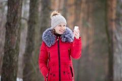 Glückliche lächelnde Frau in der roten Winterjacke schaut auf ihrem beweglichen pH Stockfotos