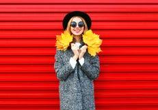 Glückliche lächelnde Frau des Modeherbstes hält gelbe Ahornblätter stockbild
