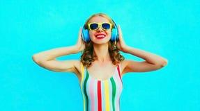 Glückliche lächelnde Frau des Porträts, die Musik in den drahtlosen Kopfhörern auf buntem Blau hört lizenzfreie stockbilder