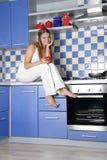Glückliche lächelnde Frau, die auf Küche kocht Stockfotografie