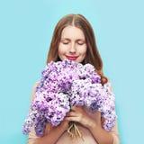 Glückliche lächelnde Frau, die lila Blumen des Geruchblumenstraußes über buntem blauem Hintergrund genießt stockfotos