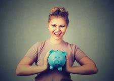 Glückliche, lächelnde Frau, die Sparschwein hält Sparguthaben, Konzept ein Bankkonto habend stockfotografie