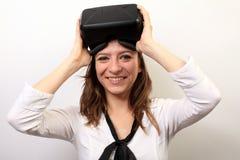 Glückliche, lächelnde Frau in einem weißen Hemd, tragender Kopfhörer virtuellen Realität 3D der Oculus-Riss-VR, es beseitigend od Stockbild