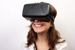 Glückliche, lächelnde Frau in einem weißen Hemd, tragender Kopfhörer virtuellen Realität 3D der Oculus-Riss-VR, lachend Stockbild