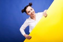 Glückliche lächelnde Frau hält ein gelbes Plakat in den Händen mit Kopienbadekurort lizenzfreies stockfoto