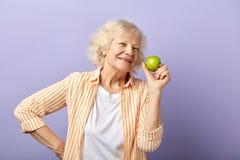Gl?ckliche l?chelnde Frau in ihre Sechziger, die gr?nen Apfel halten und an der Kamera l?cheln lizenzfreies stockbild