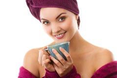 Glückliche lächelnde Frau im purpurroten Bademantel, Frische und Wohl genießend Lizenzfreies Stockfoto