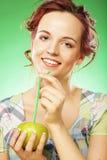 Glückliche lächelnde Frau mit Apfel und Stroh-Cocktail Lizenzfreie Stockfotografie