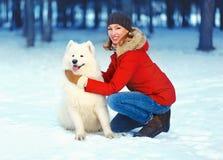 Glückliche lächelnde Frau mit dem Samoyedhund, der in Winterpark geht Stockfoto