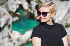 Glückliche lächelnde Frau mit schwarzer Sonnenbrille und dem Hemd, die nahe bei einem schöner Türkis farbigen Fluss aufwirft stockfotos