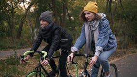 Glückliche, lächelnde Freunde oder junge Paare, die auf ihre Trekkingsfahrräder durch den Herbstpark auf Fahrrädern radfahren Man stock video