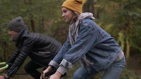 Glückliche, lächelnde Freunde oder junge Paare, die durch den Herbstpark auf Fahrrädern radfahren Reitenfahrräder des Mannes und  stock video footage