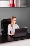 Glückliche lächelnde Geschäftsfrau, die auf Laptop an ihrem Schreibtisch schreibt Lizenzfreie Stockfotografie