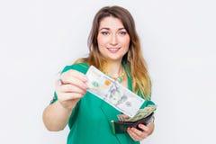 Glückliche lächelnde Geschäftsfrau, die in der grünen Jacke mit einer großen Geldbörse und einem Geld trägt Nahaufnahmeporträt su Stockfoto