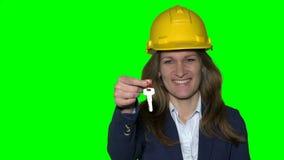 Glückliche lächelnde Geschäftsfrau oder Immobilienagentur mit dem Sturzhelm, der Schlüssel zeigt stock video
