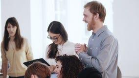 Glückliche lächelnde Geschäftsleute arbeiten, der junge aufgeregte kaukasische Mann zusammen, der während der modernen Bürosemina stock video