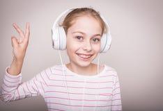 Glückliche lächelnde hörende Musik des Kindermädchens in den weißen Kopfhörern Stockfotos