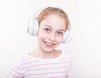 Glückliche lächelnde hörende Musik des Kindermädchens in den weißen Kopfhörern Stockfoto