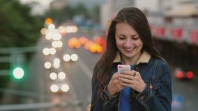 Glückliche, lächelnde hübsche Frau benutzt einen Smartphone, der auf der Brücke steht Wind brennt ihr Haar durch 4K Stockbild