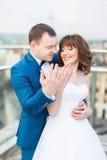 Glückliche lächelnde Hochzeitspaare auf der Terrasse, die ihre Ringe zeigt Stockfotos