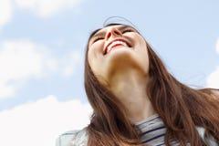 Glückliche lächelnde junge attraktive Frau über blauem Himmel Lizenzfreie Stockfotografie