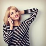 Glückliche lächelnde junge blonde Frau, die auf Handy und Blick spricht Lizenzfreies Stockbild