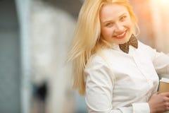 Glückliche lächelnde junge blonde Frau im weißen Hemd mit Bindung Lizenzfreie Stockfotos