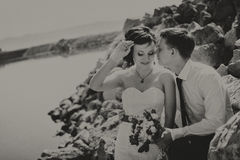 Glückliche lächelnde junge Braut und Bräutigam, gehend auf Strand, Küssen und umarmen Hochzeitszeremonie nahe Felsen, Ozean lizenzfreie stockfotos