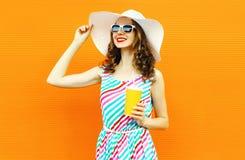 Glückliche lächelnde junge Frau des Porträts mit Schale Fruchtsaft im Sommerstrohhut, buntes gestreiftes Kleid auf orange Wand stockfotos