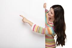 Glückliche lächelnde junge Frau, die leeres Schild zeigt Stockbilder